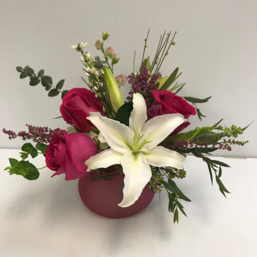 res roses and white lilies in a red vase